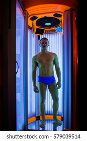 muscular man with sexy healthy body standing in solarium spa salon in blue pants, has strong muscle on chest, belly and torso