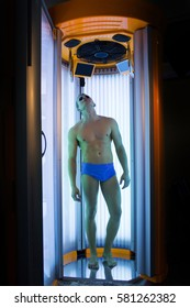 muscular man with sexy healthy body standing in solarium spa salon in blue pants and sunglasses, has strong muscle on chest, belly and torso