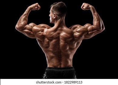 Muscular man showing back muscles, isolated on black background. Strong male rear view