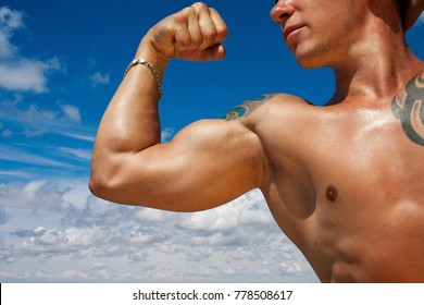 Muscular man showing biceps against the sky