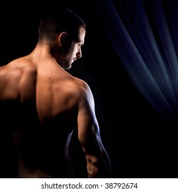 A muscular man showing his back under dramatic lights.