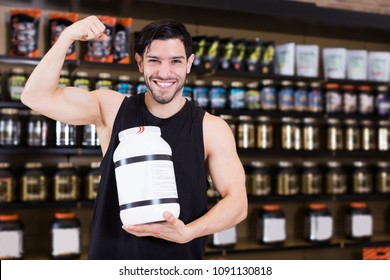 muscular man showing his biceps and holding pot of  sport nutrition in shop
