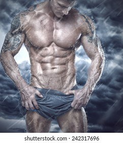 Muscular man showing his body in stormy weather