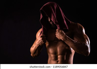Muscular man is showing his torso with towel on the head