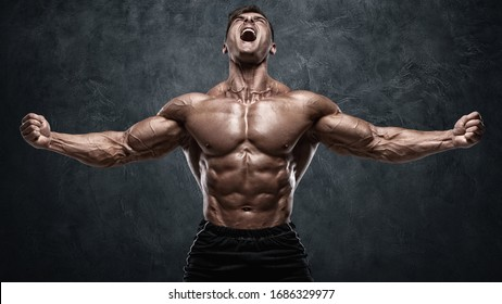 Muscular man showing muscles on wall background. Bodybuilder male naked torso abs