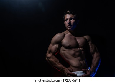 Muscular man showing muscles on black background. Concept of healthy lifestyle