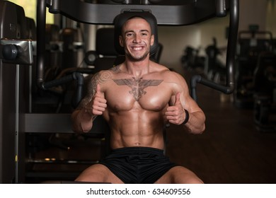 Muscular Man Showing Thumbs Up While Standing Strong In A Gym And Flexing Muscles - Muscular Athletic Bodybuilder Fitness Model Posing After Exercises