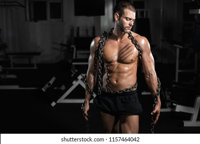 Muscular man slave in chains in gym, the prisoner, the man torn to freedom