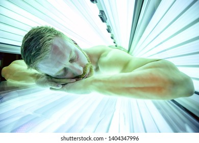 Muscular man in a solarium lying on his stomach and relaxing