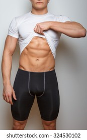 Muscular man in sportswear showing his muscular stomach.