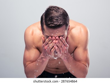 Muscular man spraying water on his face over gray background