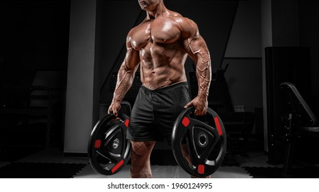 Muscular man stands in a gym with barbell discs. Bodybuilding and powerlifting concept. Mixed media