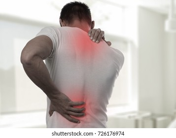Muscular Man suffering from back and neck pain. Incorrect sitting posture problems Muscle spasm, rheumatism. Pain relief, ,chiropractic concept. Sport exercising injury