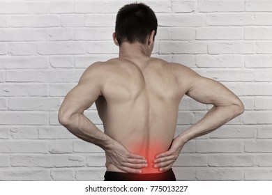 Muscular Man suffering from back and neck pain. Incorrect sitting posture problems, Muscle spasm, rheumatism. Pain relief , chiropractic concept. Sport exercising injury