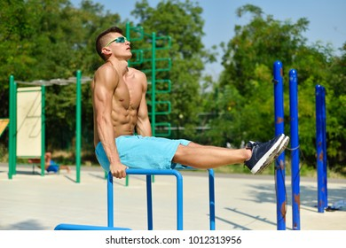 Muscular Man Swinging Press In Playground. Crossfit Concept.