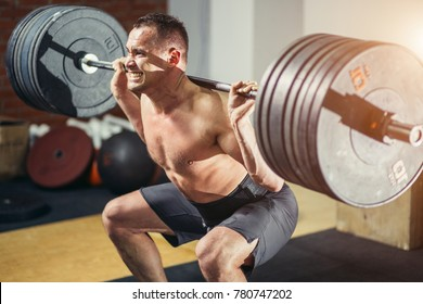 Muscular man training squats with barbells on shoulders.