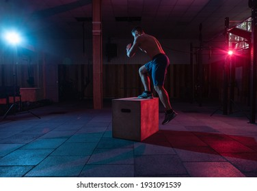 Muscular man training wooden box pacing in dark gym. Athlete workout in red blue neon light. Healthy lifestyle cross training