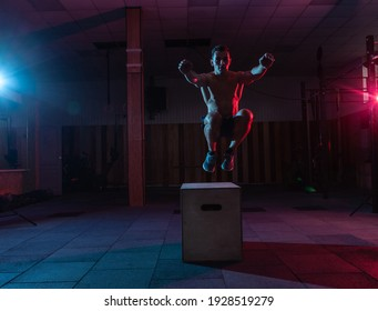 Muscular man trains jumping on a wooden box in a dark gym. Athlete Workout in red blue neon light. Cross, functional training