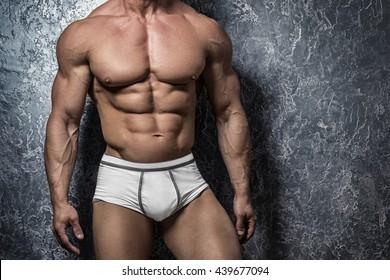 Muscular man in underwear against concrete wall