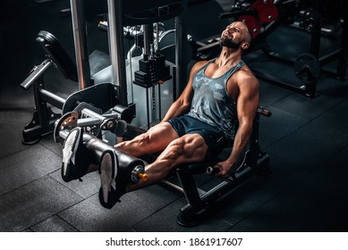 Muscular man using weights machine for legs at the gym. Hard training