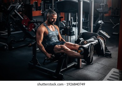 Muscular man using weights machine for legs at the gym