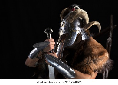 Muscular man in viking costume with horned helmet , shield and sword