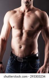 Muscular man wearing fashionable jeans posing in studio shirtless.
