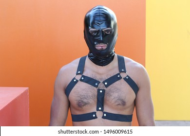Muscular man wearing leather harness and latex mask