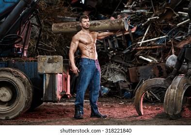 Muscular man working on junkyard