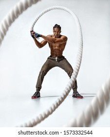 Muscular man working out with battle rope. Photo of sporty man with naked torso on grey background. Strength and motivation. Full length