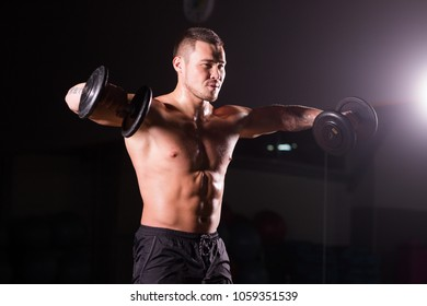 Muscular man working out in gym doing exercises with dumbbells at biceps, strong male naked torso abs.
