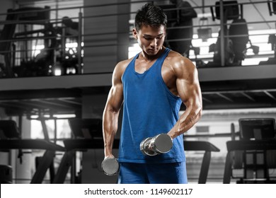 Muscular man working out in gym doing exercises for biceps, strong male