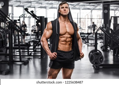 Muscular man working out in gym, strong male naked torso abs