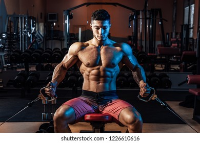 Muscular man working out in gym doing exercises. Young athletic man