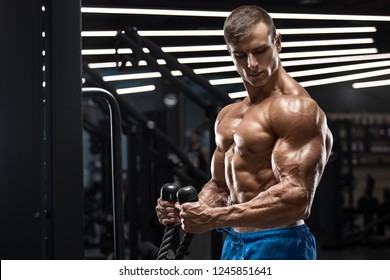 Muscular man working out in gym doing exercises for biceps, strong male naked torso abs