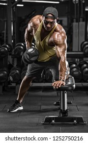 Muscular man working out in gym doing exercises for back. Single Arm Dumbbell Row