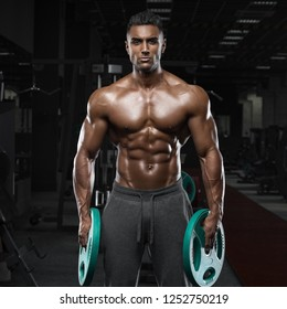 Muscular man working out in gym, strong arab male, naked torso abs
