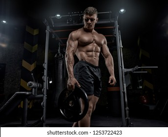 Muscular man working out in gym doing exercises, strong male naked torso abs.