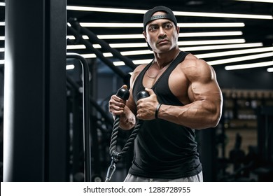 Muscular man working out in gym doing exercises for biceps. Strong male