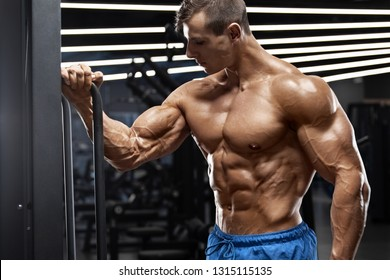 Muscular man working out in gym showing biceps. Strong male torso abs