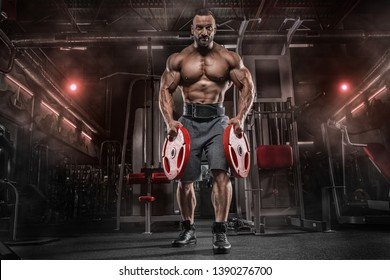 Muscular man working out in gym with tire, strong male naked torso abs
