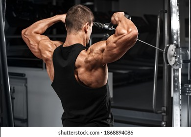 Muscular man working out in gym doing exercise for deltoid, strong male