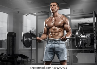Muscular man working out in gym doing exercises with barbell, strong male naked torso abs