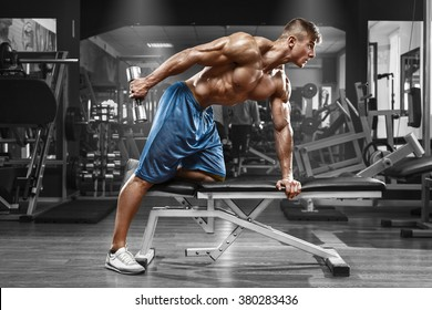Muscular man working out in gym doing exercises with dumbbells at triceps, strong male naked torso abs