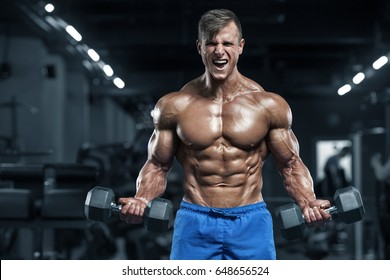 Muscular man working out in gym doing exercises, strong male torso abs