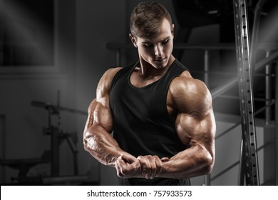 Muscular man working out in gym. Strong male showing muscles biceps