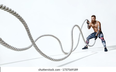 Muscular man working out with heavy ropes. Photo of handsome man with perfect body on white background. Strength and motivation. Full length