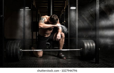 Muscular man workout with barbell at gym