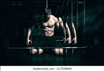 Muscular man workout with barbell at gym. Mirror effect