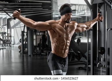 Muscular man workout in gym.